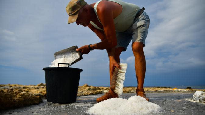 Alfred Attard mengumpulkan garam laut dari dataran garam dengan pematang batu di sebuah desa di Gozo, Malta, pada 7 September 2020. Dikelilingi seluruhnya oleh laut, Malta merupakan salah satu produsen besar garam laut yang dihasilkan dari dataran garam berpematang batu. (Xinhua/Jonathan Borg)