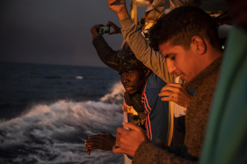 FILE - In this Sunday Jan. 12, 2020 file photo, men from Nigeria and Morocco watch the sunset aboard the Open Arms rescue vessel as the ship sails north with 118 people from different nationalities who were rescued on Friday off the Libyan coast. The European Union announced Tuesday, March 31, 2020 the launch of a new naval mission in the Mediterranean Sea aimed at enforcing the U.N arms embargo on Libya, after Italy blocked a previous operation claiming that the warships attracted migrants. (AP Photo/Santi Palacios, File)