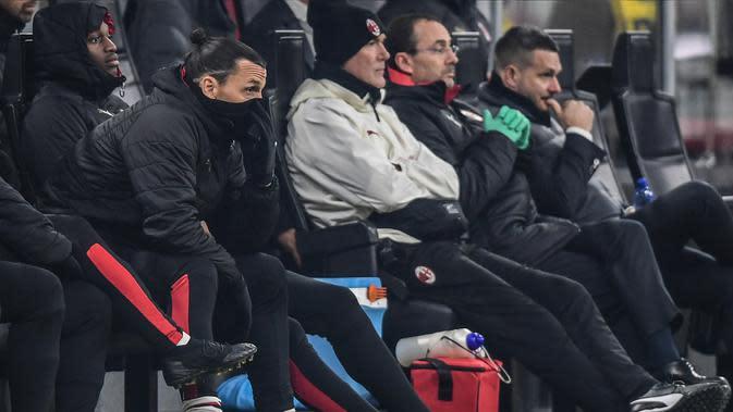 Pemain AC Milan Zlatan Ibrahimovic (kiri) menyaksikan timnya bertanding melawan SPAL dari bangku cadangan pada babak 16 besar Coppa Italia 2019/2020 di Stadion San Siro, Milan, Italia, Rabu (15/1/2020). AC Milan menang 3-0. (Miguel MEDINA/AFP)