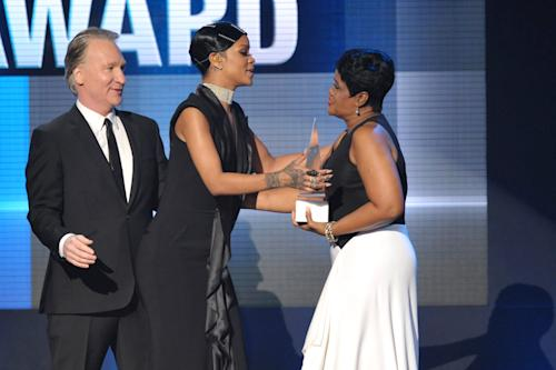 Bill Maher, left, and Rihanna's mother Monica Braithwaite, right, present the Icon award to Rihanna on stage at the American Music Awards at the Nokia Theatre L.A. Live on Sunday, Nov. 24, 2013, in Los Angeles. (Photo by John Shearer/Invision/AP)