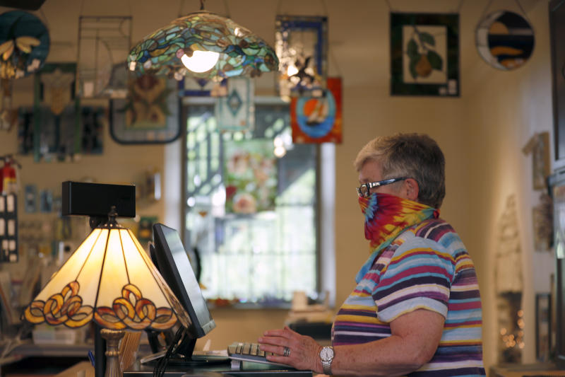 Vicki Driscoll works behind the counter at The Glass Workbench glass and gift shop Monday, May 4, 2020, in St. Charles, Mo. Businesses in many parts of Missouri were allowed to reopen after the state's stay-at-home order expired Monday allowing Driscoll to get back to work for the first time since March 21. (AP Photo/Jeff Roberson)