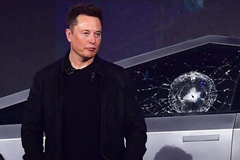 Tesla co-founder and CEO Elon Musk stands in front of the newly unveiled all-electric battery-powered Tesla's Cybertruck