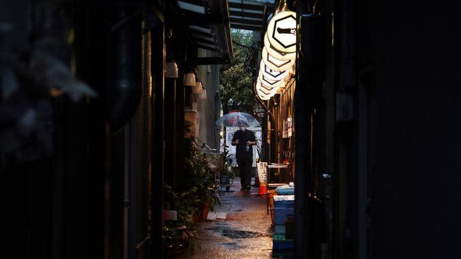 Seorang pria yang mengenakan masker untuk membantu mencegah penyebaran COVID-19 berjalan melewati gang sempit saat hujan di Tokyo, Jepang, Selasa (30/6/2020). Sebagian besar kegiatan sosial dan bisnis di Jepang telah kembali dimulai. (AP Photo/Eugene Hoshiko)