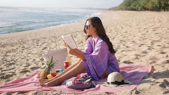 Mengikuti tren masa kini, Jessica Mila pun menggelar kain untuk piknik di pantai. Di momen pikniknya kali ini, ia nampak mengenakan jumpsuit warna ungu lilac dan mengenakan riasan natural. (Liputan6.com/IG/jscmila)