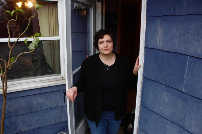 In this April 29, 2020 photo, Julie Hitchcock stands in her back doorway in Milwaukee. Hitchcock, 49, said she worries about getting sick or unknowingly infecting someone else, anxiety that's heightened because she was on a ventilator for two weeks last fall after developing pneumonia. As the coronavirus pandemic upends lives across the nation, a new poll conducted by NORC at the University of Chicago for the Data Foundation found that most Americans reported feeling nervous, depressed, lonely or hopeless in the last week. (AP Photo/Carrie Antlfinger)