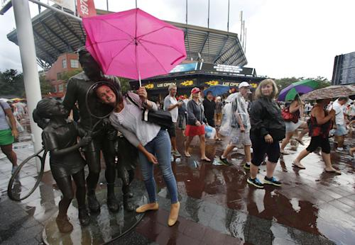 A tennis fan stops for a photo as she exits the Billie Jean King National Tennis Center during a rain delay at the 2014 U.S. Open tennis tournament, Sunday, Aug. 31, 2014, in New York. (AP Photo/Elise Amendola)