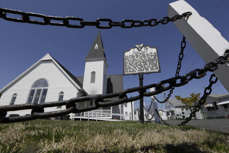 FILE - This Wednesday April 3, 2013 file photo shows a chain fence surrounding the Swain Memorial Church in Tangier Island, Va. The fishing community in the middle of the Chesapeake Bay has reported zero cases of the coronavirus. But the virus would be devastating if it were to reach the island, which has a large elderly population and no full-time doctor. (AP Photo/Steve Helber)