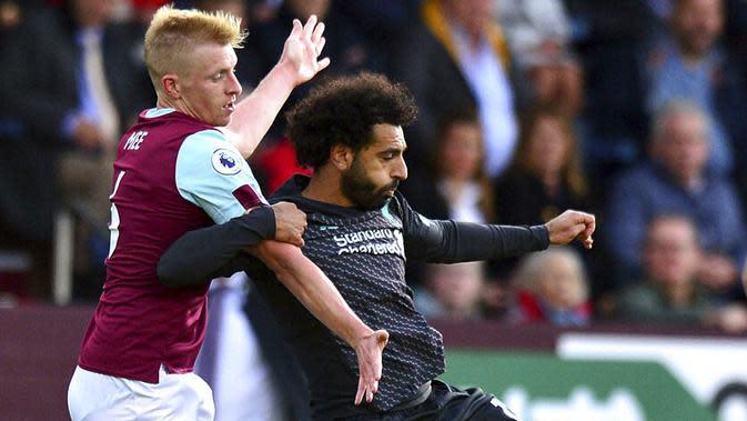 Penyerang Liverpool, Mohamed Salah, berebut bola dengan pemain Burnley, Ben Mee, pada laga Premier League 2019 di Stadion Turf Moor, Sabtu (31/8). Liverpool menang 3-0 atas Burnley. (AP/Anthony Devlin)