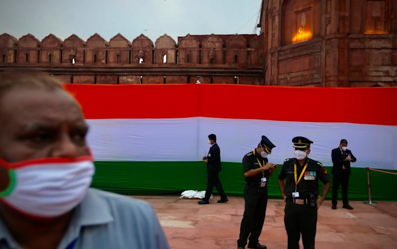 Security personnel wear masks while waiting for the start of the Independence Day ceremony at the Red Fort monument in New Delhi, India - AP Photo/Manish Swarup