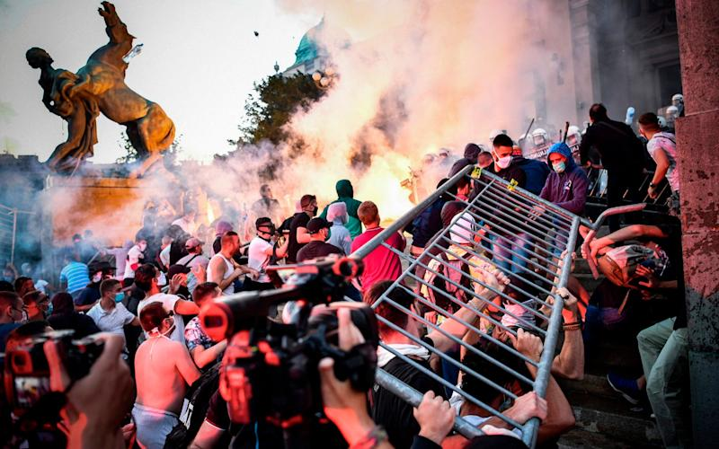 Protesters clash with police in front of Serbia's parliament in Belgrade for a second consecutive night on Wednesday over plans to re-impose lockdown to counter a surge in coronavirus - ANDREJ ISAKOVIC/AFP