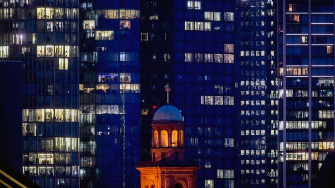 Lampu menyala pada beberapa gedung bank di Frankfurt, Jerman, Kamis (24/9/2020). Di latar depan gereja Paul. (AP Photo/Michael Probst)