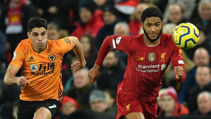 Bek Liverpool, Joe Gomez (kanan) berebut bola dengan gelandang Wolverhampton Wanderers, Pedro Neto pada pekan ke-20 Liga Inggris 2019-2020 di Anfield, Minggu (29/12/2019). Liverpool semakin perkasa di Premier League setelah menang 1-0 atas Wolverhampton. (Paul ELLIS / AFP)
