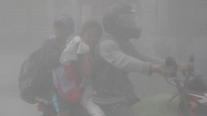 Sebuah keluarga mengendarai motor menembus abu vulkanik gunung Taal untuk mengungsi ke tempat yang lebih aman di Lemery, provinsi Batangas, Filipina, Senin (13/11/2020). Erupsi gunung Taal memaksa puluhan ribu orang mengungsi serta membuat sekolah-sekolah dan toko di Manila tutup. (AP/Aaron Favila)