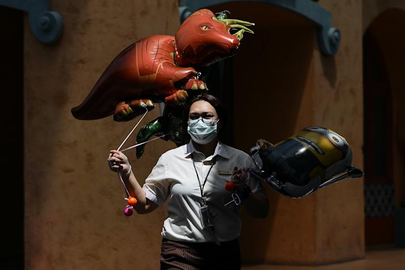 A staff wearing protective mask carries balloons for sale at Universal Studios at Resorts World Sentosa on 3 July, 2020 in Singapore. (PHOTO: Getty Images)