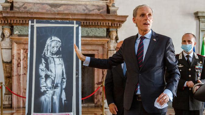 Duta Besar Prancis untuk Italia, Christian Masset, menerima dari jaksa penuntut Italia lukisan seniman Inggris Banksy yang menggambarkan sosok perempuan muda dengan ekspresi sedih di Kedutaan Besar Prancis di Roma (14/7/2020). (AP/Photo/Domenico Stinellis)