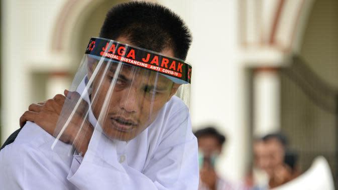 Reaksi salah seorang pasangan terpidana kasus zina saat menjalani hukuman cambuk di Masjid Al Munawarah, Kota Jantho, Aceh Besar, Jumat (4/9/2020). Pasangan terpidana yang terbukti melanggar Syariat Islam dalam kasus zina itu masing masing menjalani sebanyak 100 cambuk. (CHAIDEER MAHYUDDIN/AFP)
