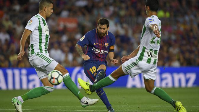 Aksi Lionel Messi (tengah) melepaskan tembakan melewati adangan dua pemain Real Betis pada lanjutan La Liga Spanyol di Camp Nou stadium, Barcelona, (20/8/2017). (AFP/Lluis Gene)