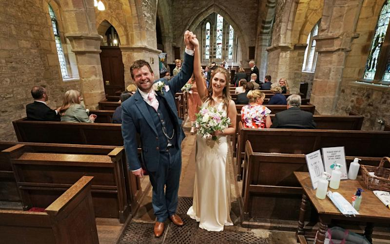 Lucy Johnston, 25, and James Bone, 28, celebrate their wedding in Northumberland on July 4, as ceremonies were again permitted, but with a maximum of 30 guests - Owen Humphreys/PA
