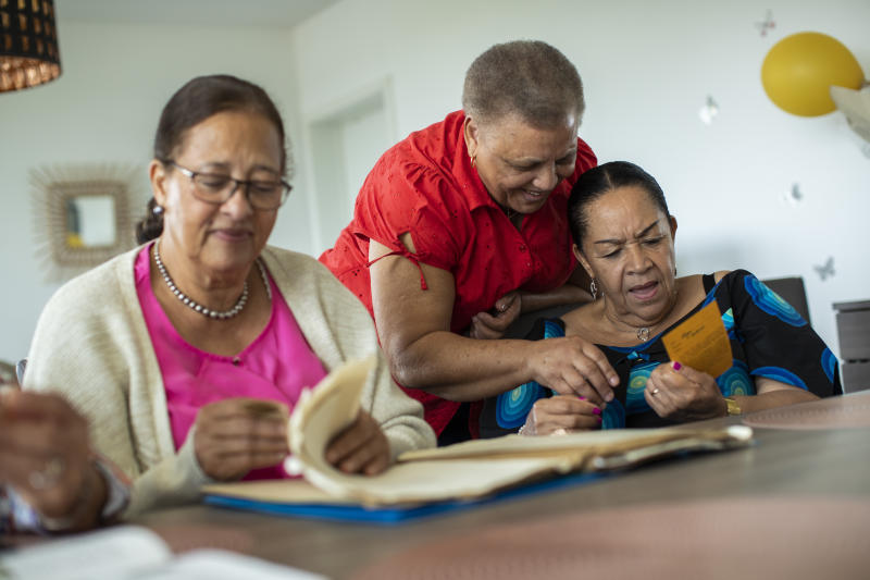 In this photo taken on Monday, June 29, 2020, Lea Tavares Mujinga, right, speaks with her friend Simone Ngalula, center, as they look over papers with Monique Bitu Bingi during an interview with The Associated Press in Brussels. The three women are part of a group of biracial women who were taken from their families as children in Belgian Congo and placed in a religious mission run by Catholic nuns who have now filed a lawsuit seeking reparations from Belgium. (AP Photo/Francisco Seco)