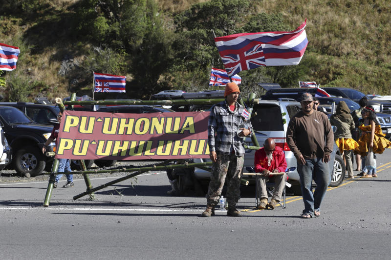FILE - In this July 14, 2019, file photo, native Hawaiian activists gather at the base of Hawaii's Mauna Kea. Opponents of the Thirty Meter Telescope project on Hawaii island have left their camp because of concerns over the spread of the coronavirus. The Honolulu Star-Advertiser reports the move came after more than eight months of nonviolent protests at the base of the Mauna Kea Access Road. (AP Photo/Caleb Jones, File)