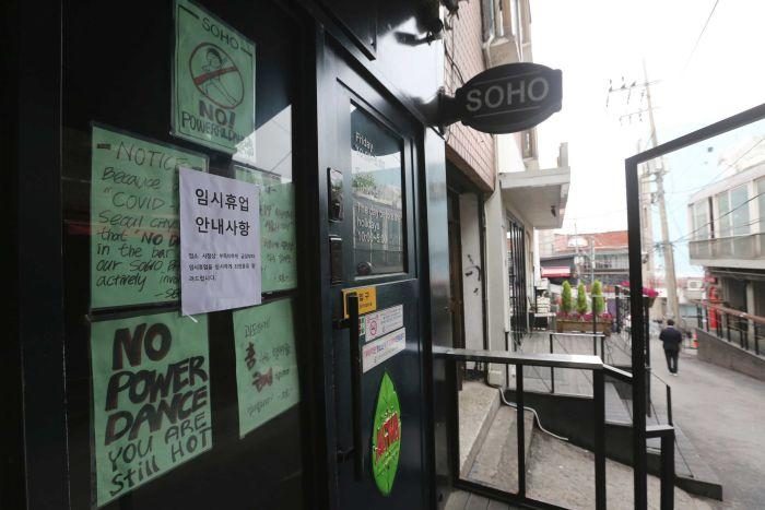 Signs posted on a closed door with messages such as 'NO POWER DANCE - YOU ARE STILL HOT'