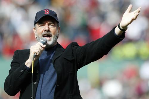 "FILE - This April 20, 2013 file photo shows Neil Diamond singing ""Sweet Caroline"" in the eighth inning of a baseball game between the Boston Red Sox and the Kansas City Royals in Boston. Sales for Neil Diamond's ""Sweet Caroline"" are up by 597 percent a week after the tune has become a source of comfort following bombings in Boston last week. The song is a staple of Boston Red Sox games. Nielsen SoundScan said Wednesday that it sold 19,000 tracks this week. It only sold 2,800 the week before. It has sold 1.75 million tracks to date. Diamond released the song in 1969. It is addressed to Caroline Kennedy. (AP Photo/Michael Dwyer, file)"