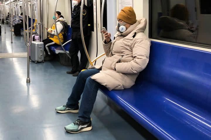 Rider using mask on transit.