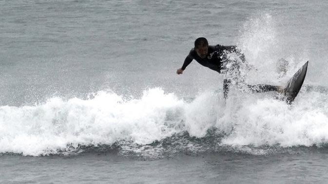 Seorang pria berselancar di pantai Katase-kaigan yang berangin, Fujisawa, Prefektur Kanagawa, selatan Tokyo, Jepang, Kamis (24/9/2020). Badai Tropis Dolphin bergerak di sepanjang pantai Pasifik Jepang. (AP Photo/Eugene Hoshiko)