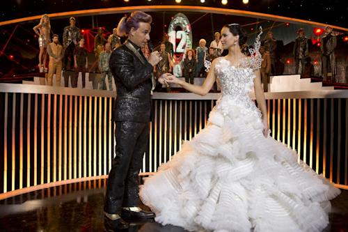 "This image released by Lionsgate shows Stanley Tucci as Caesar Flickerman, left, and Jennifer Lawrence as Katniss Everdeen in a scene from ""The Hunger Games: Catching Fire."" The film releases Nov. 22, 2013. (AP Photo/Lionsgate, Murray Close)"