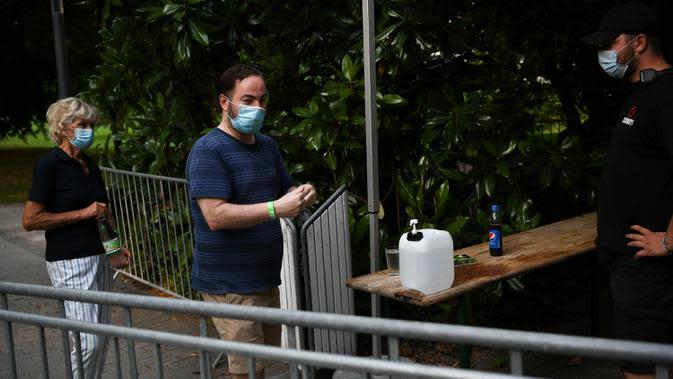 Orang-orang bersiap membersihkan tangan mereka sebelum menonton konser luar ruangan di Palm Garden di Frankfurt, Jerman, pada 1 Agustus 2020. Serangkaian konser diadakan di Frankfurt hingga 30 Agustus dengan langkah-langkah pengendalian dan pencegahan COVID-19 yang ketat. (Xinhua/Lu Yang)