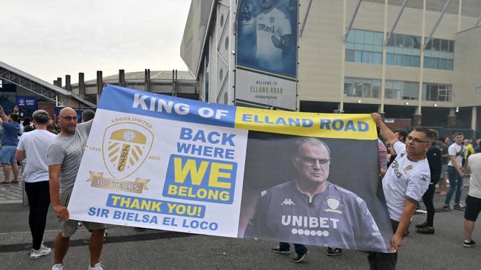 Pendukung Leeds United mengangkat spanduk besar saat mereka berkumpul di luar tanah Elland Road mereka untuk merayakan kembalinya klub ke Liga Premier setelah 16 tahun, di Leeds, Inggris utara (17/7/2020). (AFP/Paul Ellis)