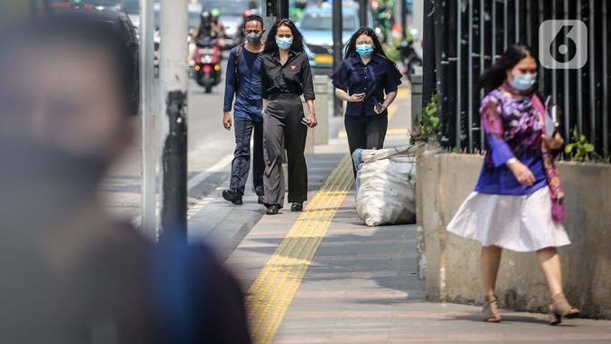 Sejumlah pegawai perkantoran di Jalan Sudirman, Jakarta, Rabu (29/7/2020). Perkantoran, khususnya kantor pemerintahan, menjadi sumber kluster baru terbesar selain permukiman dan pasar. (Liputan6.com/Faizal Fanani)