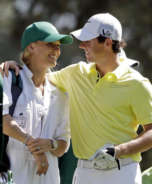 """FILE - In this April 10, 2013, file photo, Rory McIlroy, of Northern Ireland, hugs his caddie, tennis player Caroline Wozniacki, during the par-3 competition before the Masters golf tournament in Augusta, Ga. One of the top power couples in sports announced their engagement on Twitter. A spokesman for McIlroy confirmed that he popped the question in Sydney, where Wozniacki is starting to prepare for the Australian Open in Melbourne. McIlroy tweeted, """"Happy New Year everyone! I have a feeling it's going to be a great year!! My first victory of 2014."""" He added a hash tag, """"She said yes!!"""" (AP Photo/Darron Cummings, File)"""