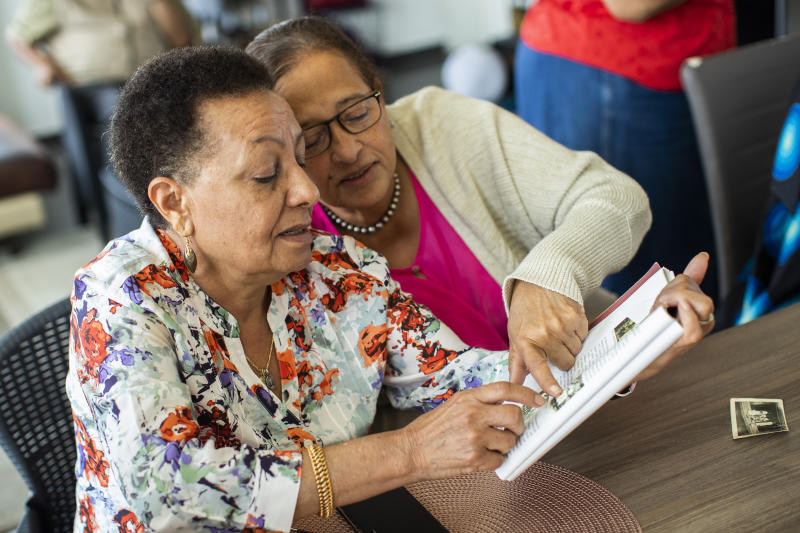 In this photo taken on Monday, June 29, 2020, Marie-Jose Loshi, left, speaks with her friend Monique Bitu Bingi as they look over old photos during an interview with The Associated Press in Brussels. The two women are part of a group of biracial women who were taken from their families as children in Belgian Congo and placed in a religious mission run by Catholic nuns who have now filed a lawsuit seeking reparations from Belgium. (AP Photo/Francisco Seco)