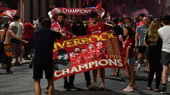Para fans merayakan Liverpool memenangkan gelar juara Liga Primer Inggris di luar stadion Anfield di Liverpoo (25/6/2020). Liverpool meraih mahkota juara Liga Premier Inggris setelah mengakhiri gelar selama 30 tahun penantian. (AFP Photo/Paul Ellis)