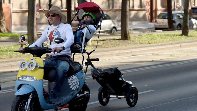 Seorang pria bersama anaknya ikut serta dalam parade kendaraan listrik di Wina, Austria, 13 September 2020. Ratusan kendaraan listrik ambil bagian dalam parade E-Mobility