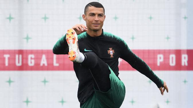 Pemain Portugal, Cristiano Ronaldo melakukan peregangan otot kaki saat sesi latihan perdana jelang Piala Dunia 2018 di base camp mereka di Kratovo, pinggiran Moskow, Rusia, Minggu (10/6). (Francisco LEONG/AFP)