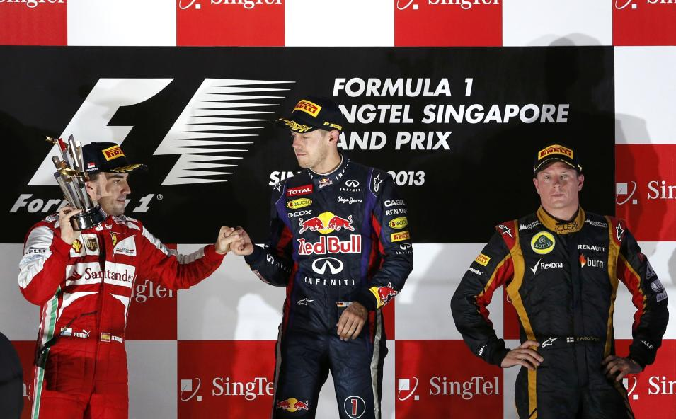 Red Bull Formula One driver Vettel, Ferrari Formula One driver Alonso and Lotus F1 Formula One driver Raikkonen stand on the podium after the Singapore F1 Grand Prix in Singapore