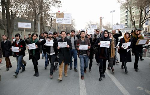 Afghan members of civil society organizations chant slogans as they march in a street, during an anti terrorism demonstration in Kabul, Afghanistan, Sunday, Jan. 19, 2014. Hundreds of Afghans gathered outside a Lebanese restaurant in Kabul on Sunday to protest against Taliban attack that killed 21 people. The assault Friday by a Taliban bomber and two gunmen against the La Taverna du Liban restaurant was deadliest single attack against foreign civilians in the course of a nearly 13-year U.S.-led war there now approaching its end. They chanted slogans against terrorism as they laid flowers at the site of the attack. The dead included 13 foreigners and eight Afghans, all civilians. The attack came as security has been deteriorating and apprehension has been growing among Afghans over their country's future as U.S.-led foreign forces prepare for a final withdrawal at the end of the year. (AP Photo/Massoud Hossaini)