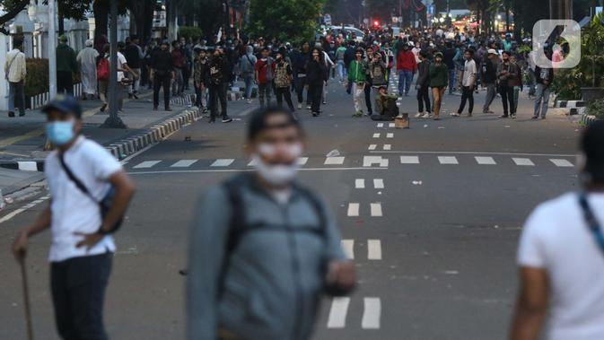 Sekelompk anak muda memancing kericuhan dengan aparat di sekitar kawasan Gindangdia, Jakarta, Selasa (13/10/2020). Sejumlah pemuda diamankan polisi karena dicurigai terlibat kericuhan di kawasan Tugu Tani. (Liputan6.com/Helmi Fithriansyah)