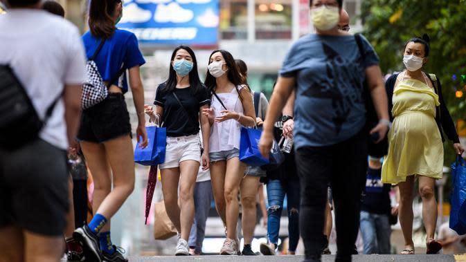 Dua wanita mengenakan masker sebagai tindakan pencegahan Covid-19 saat berjalan di Hong Kong (13/5/2020). Dua orang di Hong Kong dinyatakan positif Covid-19, mengakhiri perjalanan 24 hari tanpa kasus baru yang mulai melonggarkan peraturan jarak sosial. (AFP/Anthony Wallace)