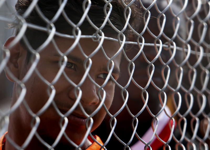 A migrant stands behind a fence inside a refugee camp in Kokkinotrimithia outside of capital Nicosia, Cyprus, on Tuesday, June 23, 2020. Cyprus' interior minister says he has asked police to launch a criminal probe into allegations that underage girls staying at a migrants' reception center were sexually harassed by other adults staying there. (AP Photo/Philippos Christou)