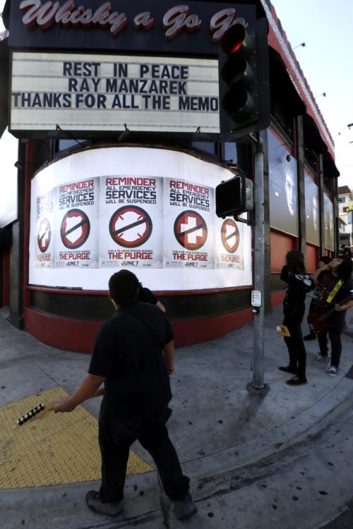 Young musicians walk past the Whisky a Go Go marquee honoring musician Ray Manzarek of The Doors Monday, May 20, 2013 in Los Angeles. Ray Manzarek, the keyboardist and founding member of The Doors who had a dramatic impact on rock 'n' roll, has died. He was 74. The Doors were the Whisky a Go Go opening band in 1966. (AP Photo/Damian Dovarganes)