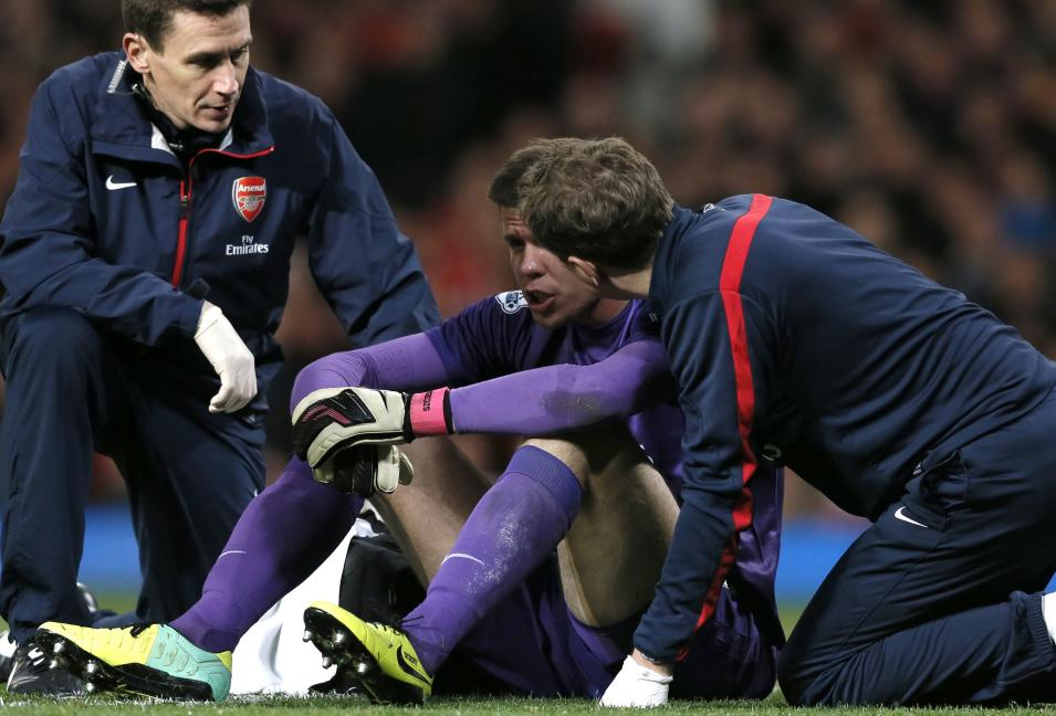 Arsenal medics talk with Szczesny after a clash of heads with Manchester United's Jones during their English Premier League soccer match in Manchester