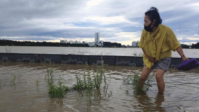Seorang warga berjalan melewati area banjir di Gangneung, Korea Selatan, Kamis (3/9/2020). Topan Maysak saat ini sedang bergerak menuju ke sisi timur semenanjung ke Laut Jepang, yang dikenal sebagai Laut Timur di Korea, dengan kecepatan hingga 140 KM per jam. (Lee Hae-yong/Yonhap via AP)