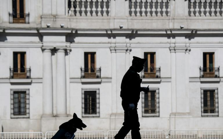 A policeman and his dog stand guard outside La Moneda presidential palace in Santiago on Wednesday