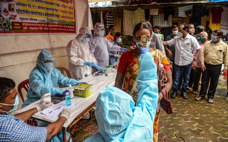 A health worker wearing a Personal Protective Equipment (PPE) suit checks the body temperature of a resident (C) during a COVID-19 coronavirus screening in Mumbai on August 12, 2020. (Photo by INDRANIL MUKHERJEE / AFP) - Indranil Mukherjee/AFP