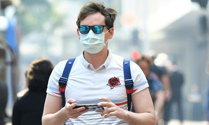 A man seen wearing a dust mask as smoke haze from bushfires in New South Wales blankets the CBD in Sydney on Tuesday.