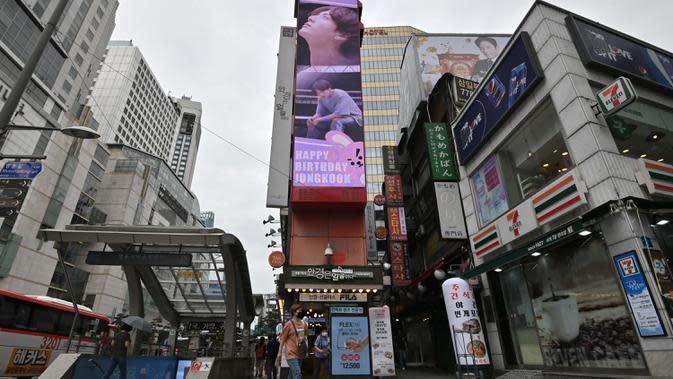 Seorang perempuan melewati layar listrik besar bergambar personel boyband BTS, Jeon Jung-kook, di sebuah distrik perbelanjaan di Seoul, Selasa (1/9/2020). Bangtan Boys (BTS) menjadi artis Korea Selatan pertama yang berhasil menempati puncak Billboard Hot 100 dengan lagu Dynamite. (Jung Yeon-je/AFP)