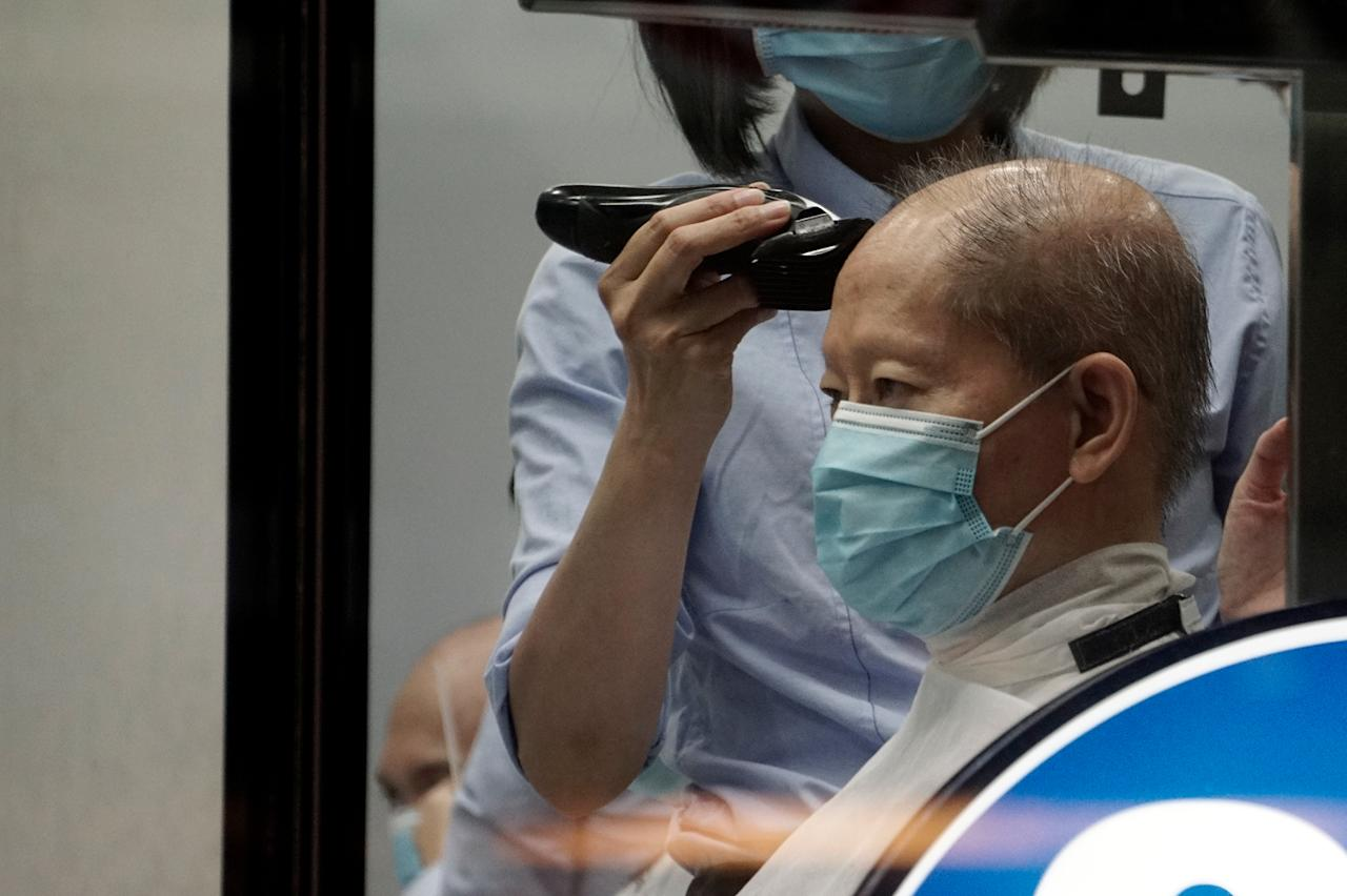 A man seen getting a haircut at a barber shop in Chinatown on 12 May 2020. (PHOTO: Dhany Osman / Yahoo News Singapore)